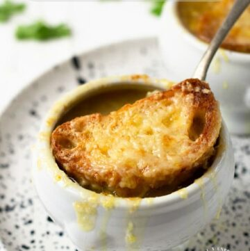 white bowl full of french onion soup topped with melted cheese and crisp french baguette