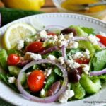 Greek salad on plate with lettuce, celery, sliced red onion, kalamatta olives, feta cheese and dressing