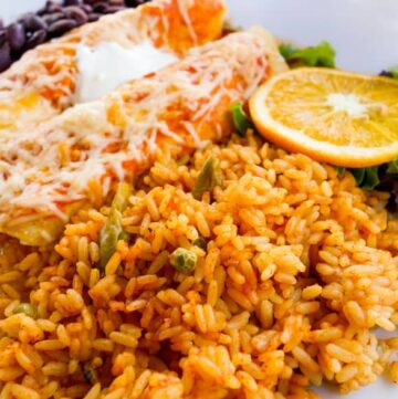 2 chicken enchiladas with fried rice on a plate