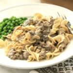 ground beef stroganoff over egg noodles with a side of peas on white plate