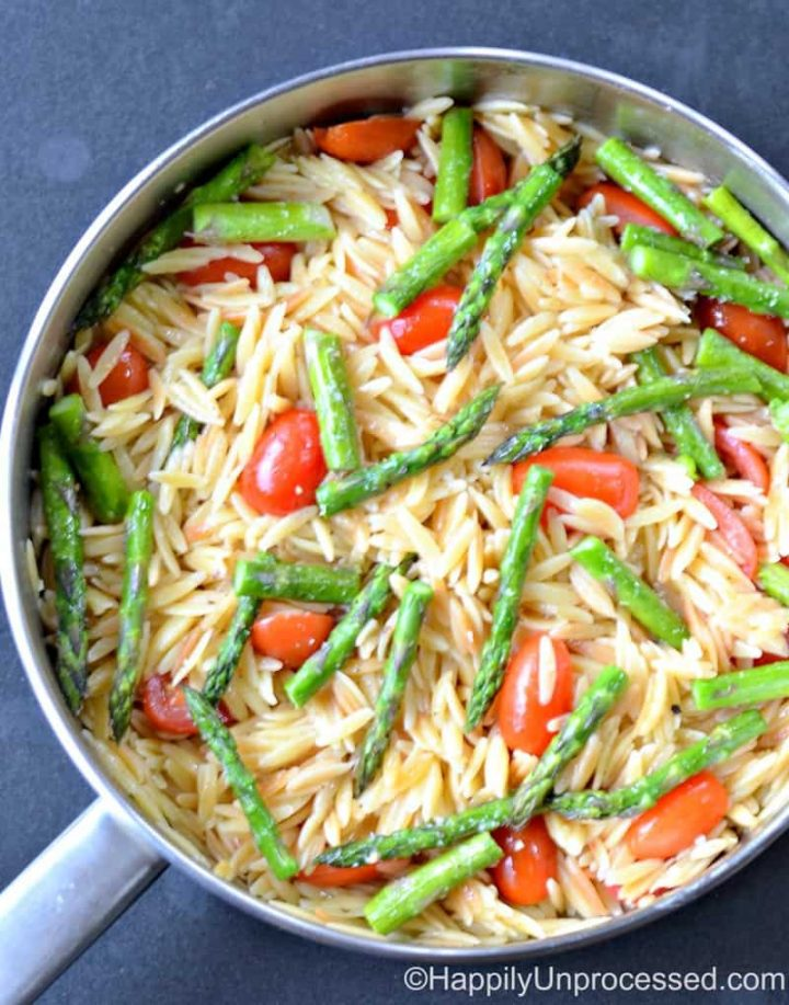 Overhead shot of lemon orzo with asparagus and cherry tomatoes