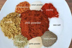 Plate with onion powder, paprika, red pepper flakes, cumin, chili powder, salt, oregano, garlic powder, black pepper