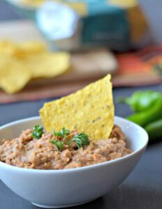 refried beans in white bowl with tortilla chips and jalapeno pepper