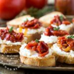 cheese on crusty bread topped with roasted tomato crostini