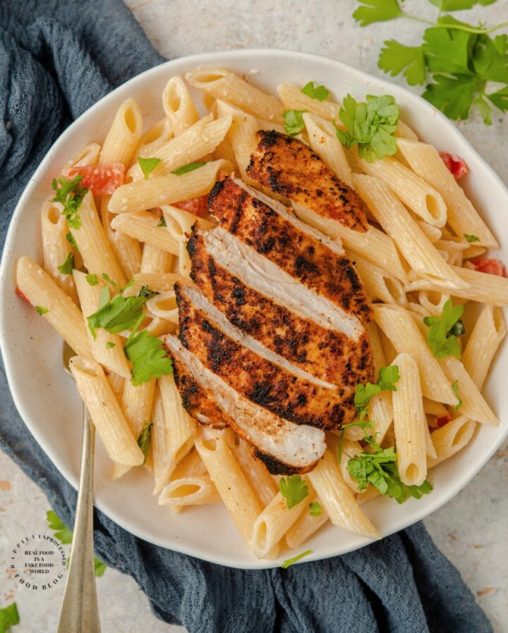 Blackened Chicken with dry rub spices charred on top of a bed of penne pasta in a bowl with olive oil, parmesan cheese and tomatoes #blackenedchicken #cajunchicken #lowcarb #ketofriendly #whole30 #paleo #glutenfree