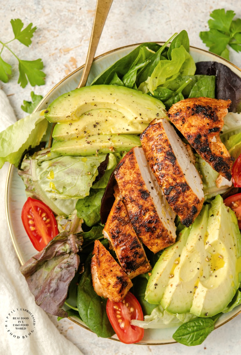 Blackened Chicken with dry rub spices charred on top of a bed of greens, sliced avocado and olive oil #blackenedchicken #cajunchicken #lowcarb #glutenfree #ketofriendly #whole30 #paleo