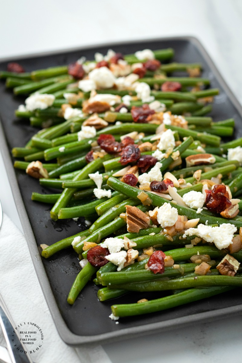 NOT YOUR MAMAS GREENBEANS - Fresh green beans topped with a Dijon Mustard Balsamic glaze, pecans, dried cranberries and feta cheese #thanksgiving #thanksgivingsides #greenbeans