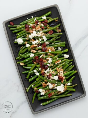 NOT YOUR MAMAS GREENBEANS - Fresh green beans topped with a Dijon Mustard Balsamic glaze, pecans, dried cranberries and feta cheese