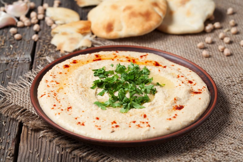 Delicious hummus creamy eastern traditional food in bowl with pita