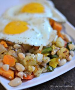 closeup sweet potato veggie hash with cannellini beans, onions, potatoes, 2 eggs on white plate