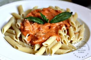 white bowl full of pasta with ala vodka sauce on top with basil