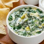 bowl of spinach artichoke dip on cutting board with tortilla chips