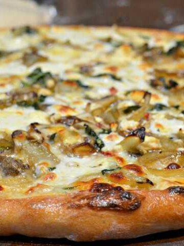 slice of caramelized onion, mushroom, feta pizza with white cream sauce