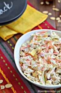 white bowl of coleslaw with apples, cranberries and almonds on festive placemat