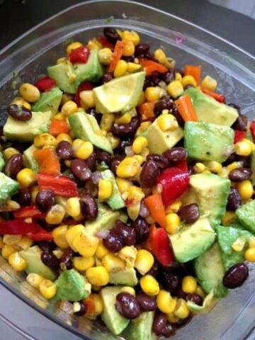 bowl of cowboy caviar grilled corn, halved cherry tomatoes, cilantro, black beans dressing