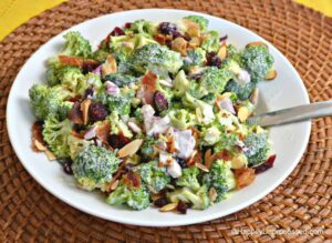 white plate with crisp fresh broccoli, slivered almonds, red onion, bacon in dressing