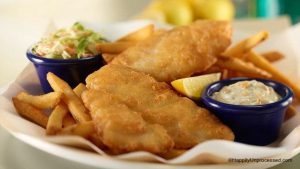 White plate with 3 stips beer battered fish, french fries, coleslaw and tartar sauce