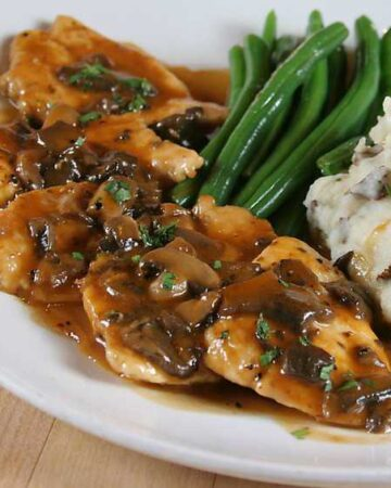 plate of chicken marsala topped with mushrooms, red skinned mashed potatoes and green beans