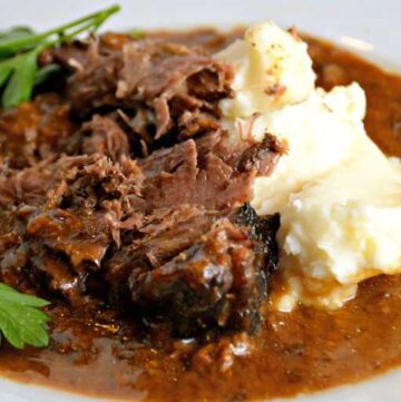 white plate with slow cooker pot roast, gravy and mashed potatoes