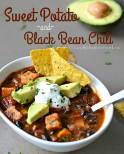 white bowl of sweet potato black bean chili topped with avocado and sour cream