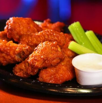 Black plate of buffalo chicken wings with celery and small bowl of ranch dressing