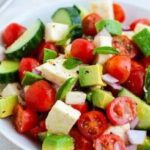 Tomato, cucumber, mozzarella cheese salad with avocado and basil in bowl