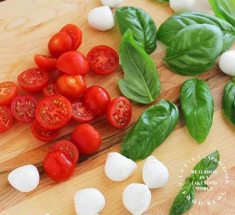 fresh ripe grape tomatoes, basil and fresh mozzeralla on cutting board