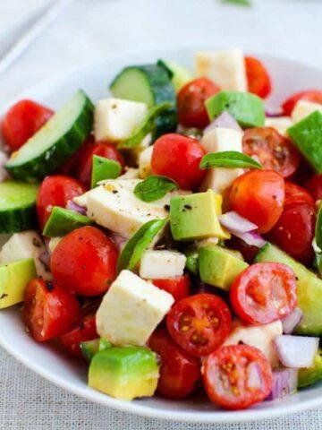Tomato, cucumber, mozzarella cheese salad with avocado and basil in bowl