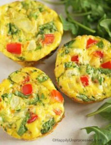 Scrambed eggs with tomatoes, onion, spinach cooked in muffin tin shaped like cupcake