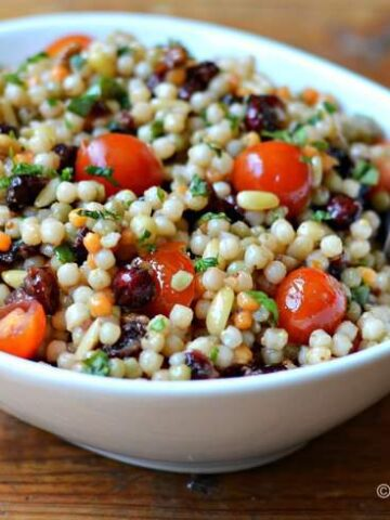 White bowl filled with Israeli couscous, diced cherry tomatoes