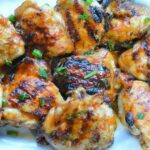 Grilled huli huli chicken on white platter with scallions