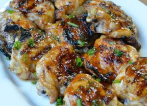 Grilled huli huli chicken on white platter with scallions