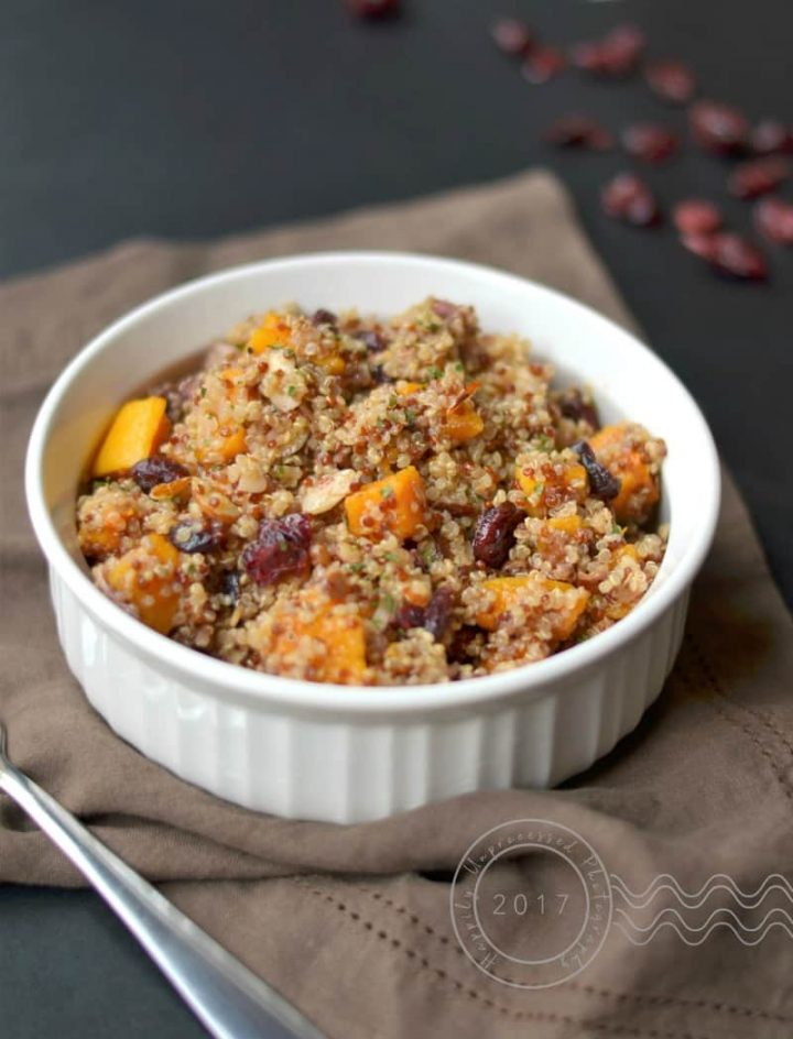 Roasted butternut squash with quinoa, dried cranberries, toasted almonds in white bowl with brown napkin