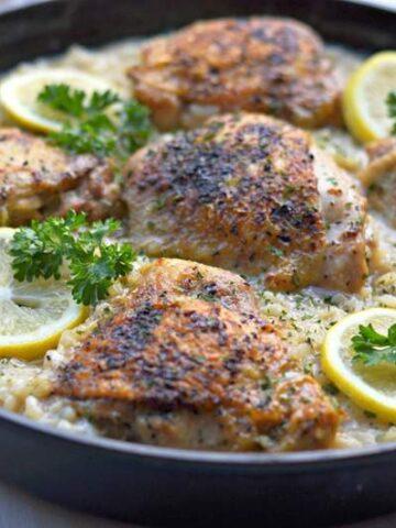 Large cast iron skillet chicken thighs lemon pepper risotto garnished with lemons