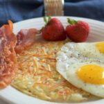 White plate with crispy golden shredded hashbrowns, 2 eggs sunny side up, 2 slices bacon, 2 strawberries with blue napkin and glass of milk