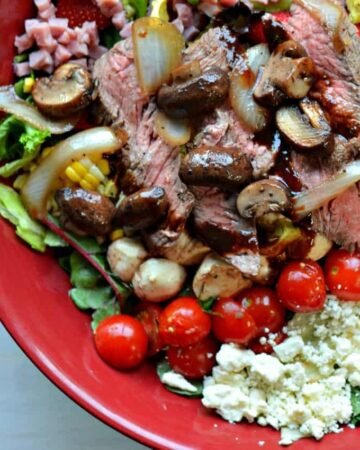 close up caprese steak salad sauteed mushrooms onions, lettuce, tomatoes, bacon in reduced balsamic dressing