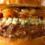 close up hamburger topped with feta cheese caramelized onions and toasted bun