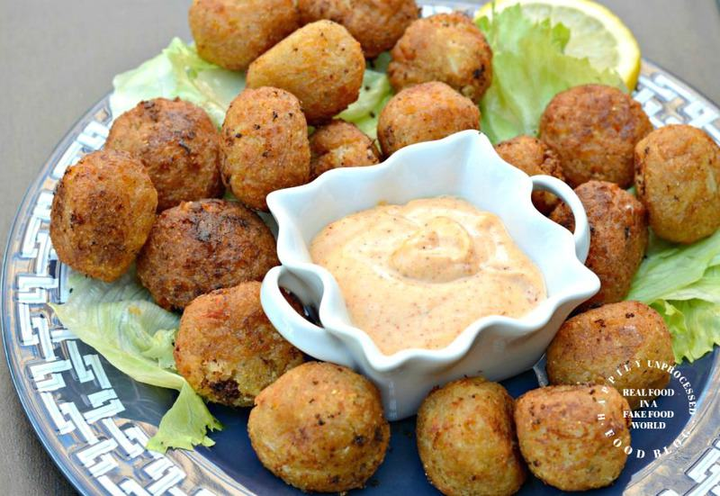 remoulade sauce in white bowl on blue plate next to fried shrimp cakes