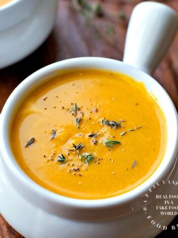 white bowl filled with roasted butternut squash sweet potato carrot soup topped with chives