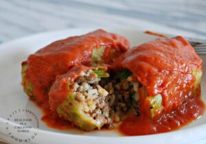 stuffed cabbage leaves with ground beef and rice topped with tomato based sauce on a plate
