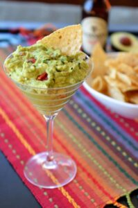 stemmed glass with homemade guacamole and tortilla chip