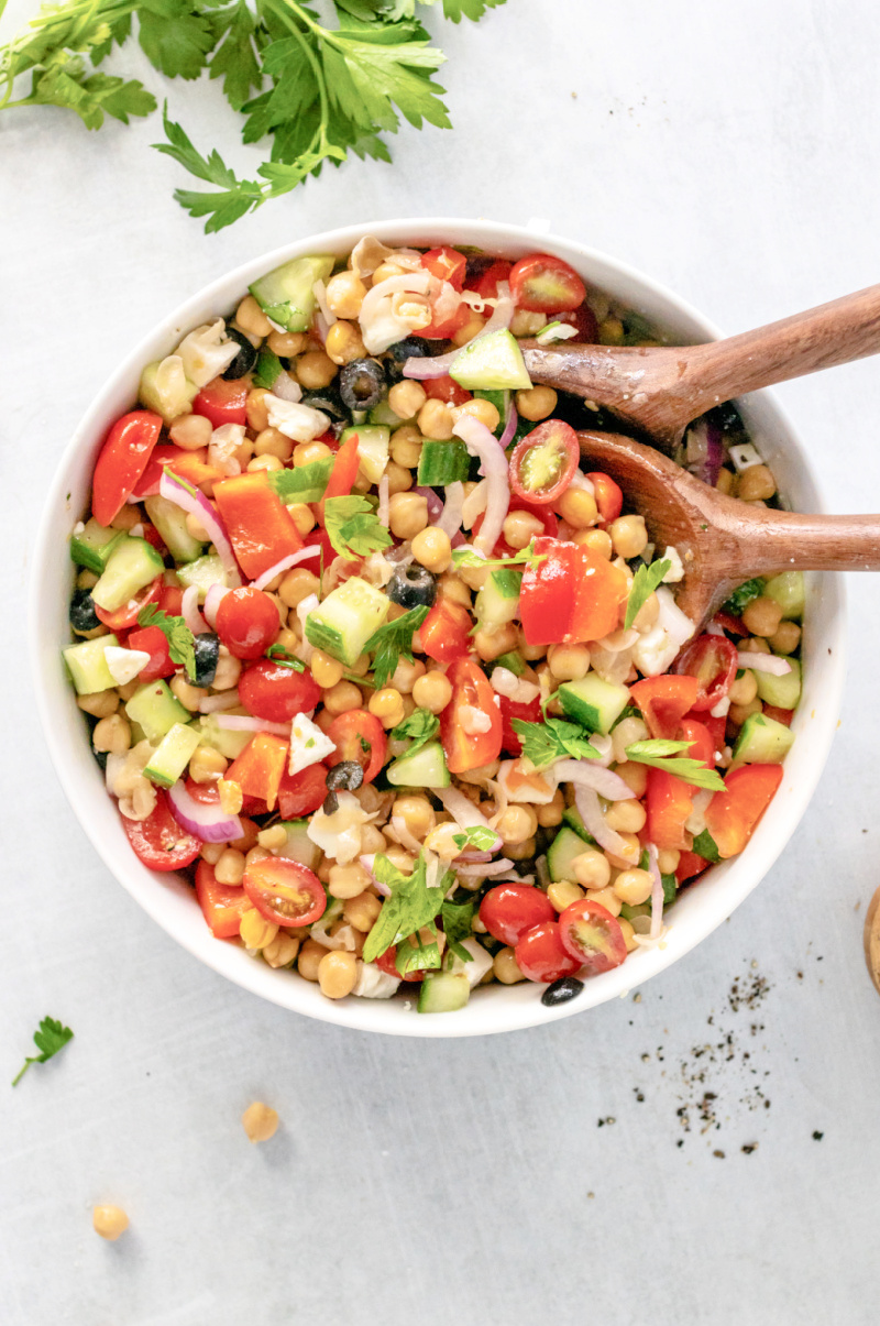 A Mediterranean Chickpea and Feta Salad in a bowl mixed with dressing - Mediterranean Chickpea & Feta Salad