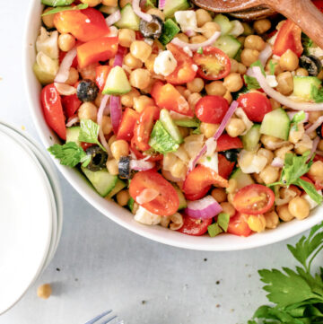 Mediterranean Chickpea and Feta Salad combined with a vinaigrette dressing in a bowl #chickpeasalad #summersalad #happilyunprocessed
