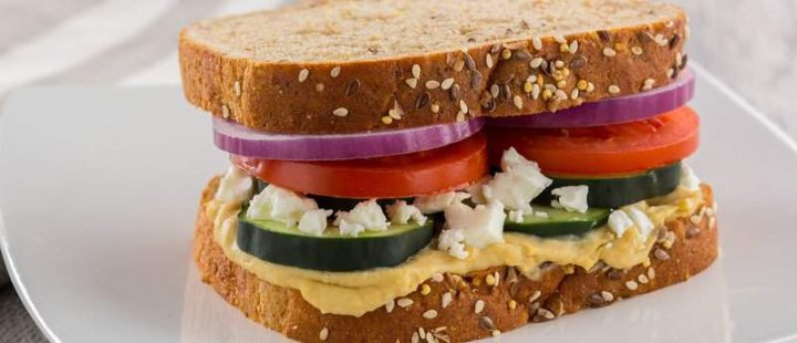 veggie sandwich with onion, tomato, cucumber, feta cheese and roasted red pepper hummus on whole wheat bread