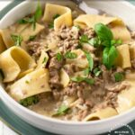 Hamburger Helper Beef Stroganoff in a white bowl with large egg noodles and garnished with parsley