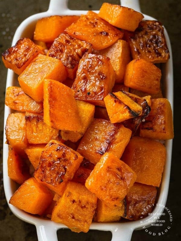 white casserole dish with roasted caramelized butternut squash