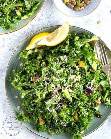 An easy lemony garlic kale salad with pistachios, pine nuts, dried cranberries topped with shaved parmesan cheese #newyearsresolution #kale #salad #healthy #happilyunprocessed