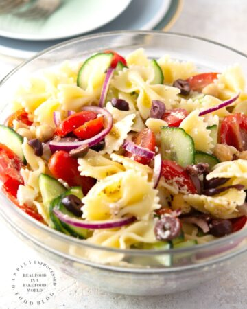 MEDITERRANEAN PASTA SALAD with bowtie pasta, red onion, cucumbers, cherry tomatoes, chick peas and feta cheese in a lemony vinaigrette #pastasalad #summer #sidedish #healthysidedish #happilyunprocessed