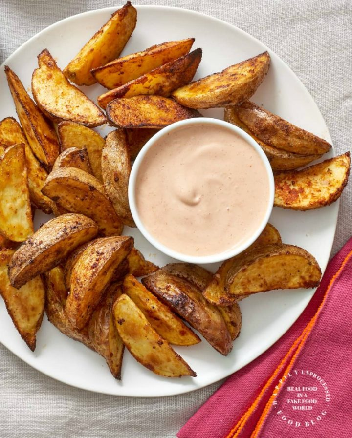 perfectly seasoned and roasted steak fries from Yukon Gold potatoes on a plate with dipping sauce