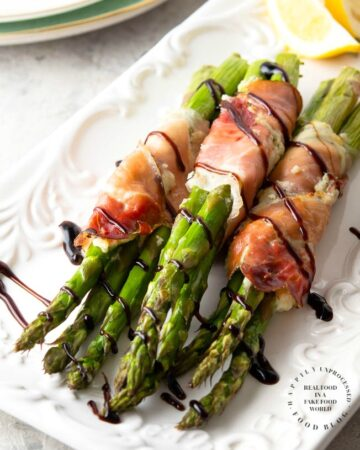 PROSCIUTTO WRAPPED ASPARAGUS - Garlic and Herb cheese is spread over prosciutto and then wrapped around fresh asparagus and baked until tender #asparagus #prosciutto #appetizer #happilyunprocessed